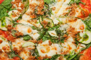 raw pizza with squash and tomato sauce